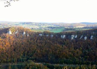 Von erhöhtem Standpunkt aus blickt man auf einen steilen, bewaldeten Rücken, auf dessen Kuppe mehrere weißlich graue Felsnasen sichtbar sind. Im Hintergrund sind weitere, aber flachere Höhenzüge erkennbar.