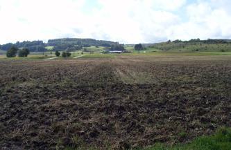 Blick über weite, dunkelbraune Äcker, die bis zum Hintergrund reichen. Dort schließt sich eine tiefer liegende, begrünte Landschaft an mit bewaldetem Hügel links und einem zweiten, von Gebüsch durchsetzten Hügel rechts.