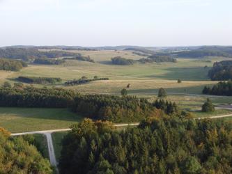 Von erhöhtem Standpunkt aus blickt man auf eine ausgedehnte, hügelige Grünlandschaft, die von Waldinseln und Wegen durchzogen ist und bis zum Horizont reicht.