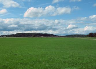 Das Bild zeigt weite, flache Wiesen unter stark bewölktem Himmel. Im Hintergrund sind dünne Ackerstreifen sowie flache bewaldete Höhenrücken erkennbar.