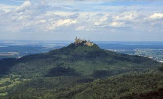 Blick von erhöhtem Standort auf einen bewaldeten Vulkankegel mit einer Burg auf der Spitze. Im Hintegrund befindet sich unter einem bewölkten Himmel Landschaft mit bewaldeten Bergrücken und Grünflächen.