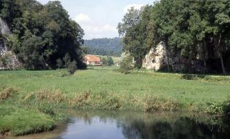 Das Bild zeigt eine an Wasser grenzende Wiese mit dahinter rechts und links aufragenden, felsigen Waldhängen. Zwischen den Felsen geht der Blick auf Gebäude, Wiesen und weitere bewaldete Höhen.