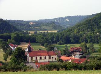 Im Mittelgrund nach links und rechts ansteigende, steile bewaldete Hänge geben den Blick frei für weitere Hänge (mit Burg) und Höhenzüge (mit Felsen). Im Vordergrund befindet sich ein kleines Dorf mit Kirche.