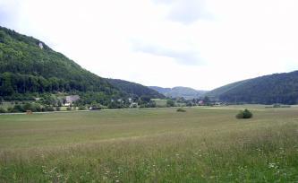 Das Bild zeigt weite, flache Wiesen. Im Hintergrund rechts öffnet sich - eingerahmt von zwei bewaldeten Hangrücken - ein ebenfalls bewaldetes Tal.
