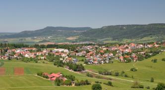 Das Bild zeigt mehrere Ortschaften, die sich - inmitten von Grünland- und Ackerflächen - zu Füßen markanter, bewaldeter Höhenzüge ausbreiten.