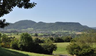 Blick über eine hügelige Landschaft mit Bäumen, Wiesen, Wald und fernen Siedlungen. Im Hintergrund erheben sich von rechts flache, bewaldete Höhen mit scharfer Kante. Weiter links und mittig liegen eine kleine und dann eine größere runde Bergkuppe auf.