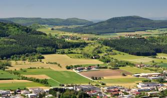 Das Bild zeigt eine aus großer Höhe aufgenommene wellige Ackerlandschaft mit Besiedlung im Vordergrund sowie Waldflächen rechts und einer bewaldeten Höhe links. Im Hintergrund sind weitere bewaldete Anhöhen gut erkennbar.