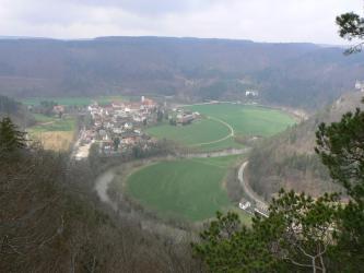 Von erhöhtem Standpunkt aus blickt man auf eine flache, teils besiedelte und teils grüne Talaue, die ein Fluss C-förmig durchquert. Steile, bewaldete Höhenzüge umrahmen die Aue. Im Zentrum der Siedlung liegt ein Kloster.