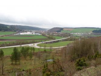 Das Bild zeigt Siedlungen, Straßen und Brücken, aber nur wenige ackerbauliche Nutzflächen. Zum Betrachter hin steigt ein von Bäumen und Hecken bestandener Hang auf. Im Hintergrund sind teils bewaldete, teils grüne Hänge zu sehen.