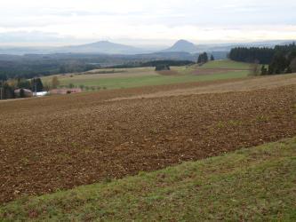 Das Bild zeigt mehrere nach rechts ansteigende Äcker; teils braun, teils begrünt. Im Hintergrund sind ausgedehnte Waldflächen sowie zwei pyramidenförmige Erhebungen erkennbar.