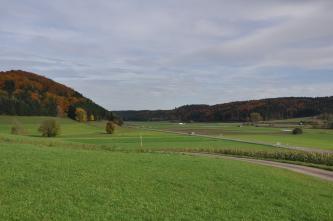 Das Bild zeigt eine nach links ansteigende Acker- und Grünlandschaft. Links erhebt sich zudem ein bewaldeter Hang. Im Hintergrund und rechts ziehen sich weitere, jedoch flachere Hänge entlang.