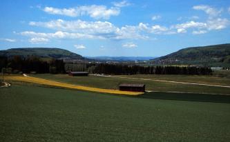 Eingefasst von zwei bewaldeten Anhöhen breitet sich eine grüne, von Waldstreifen durchzogene, bewirtschaftete Landschaft aus. Im Hintergrund, zwischen den Höhen, sind Siedlungen und Berge zu erkennen.