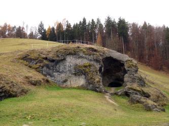 Auf einem grünen, nach rechts abfallenden Hang sitzt ein mächtiger, mit Gras und Moos bewachsener, grauer Felsen. Rechts weist der Fels eine Höhlenöffnung auf, die in die Tiefe führt. Im Hintergrund steht Wald.
