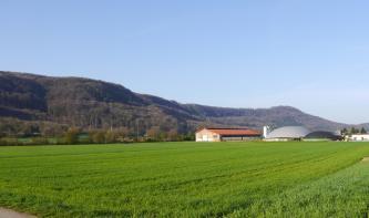 Über flache begrünte Äcker blickt man auf nach links ansteigende, bewaldete Höhenzüge. Rechts sind Industriebauten erkennbar.