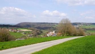 Links eines Fahrweges geht der Blick in ein besiedeltes Tal mit Acker- und Grünlandflächen, das zum Bildrand stark ansteigt. Auch rechts und im Hintergrund steigt die Landschaft an; links ist der Rücken durchgehend bewaldet.