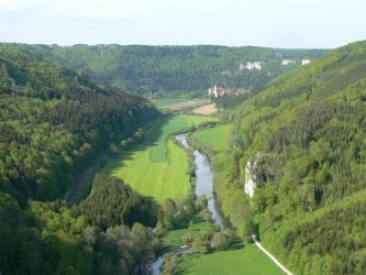 Blick von hoch oben auf ein von bewaldeten Berghängen eingerahmtes Flusstal mit Auenwiesen. An den Waldhängen rechts und im Hintergrund tritt teilweise helles Felsgestein hervor. Im Hintergrund steht zudem eine Klosterkirche.