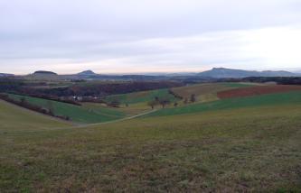 Das Bild zeigt eine weite, von links nach rechts erst absinkende und dann wieder ansteigende Acker- und Grünlandschaft. Im Hintergrund sind ein bewaldeter Hügel sowie zwei Vulkanberge erkennbar.