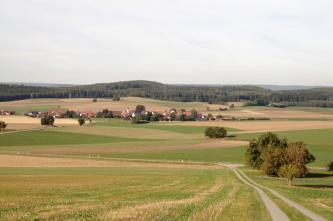Blick von leicht erhöhtem Standpunkt auf hügelige Landschaft. Im Vordergrund befinden sich teilweise begrünte Felder, im Mittelgrund eine kleine Siedlung und im Hintergrund bewaldete Hügel.