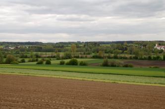 Blick in eine ebene Landschaft. Im Vordergrund ist ein Acker zu sehen, dahinter schließen sich Wiesen mit kleinen Baumgruppen an.