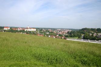 Blick über nach rechts abfallende grüne Wiesen auf eine stark besiedelte Landschaft. Links ragt ein erhöht stehendes größeres Gebäude hervor, rechts ein bewaldeter Hügel.