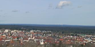 Das Bild zeigt im Vordergrund eine große Stadt und anschließende, weite Nadelwälder, Im Hintergrund ist eine Hochebene mit Windrädern erkennbar.