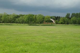 Unter einem Gewitterhimmel liegt eine flache grüne Wiese mit angrenzendem, begrüntem Damm und dichtem Baumbestand. Zwischen den Bäumen ist eine hölzerne Bogenbrücke sichtbar.