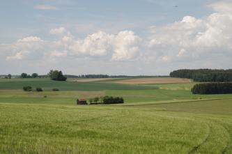 Blick über eine grüne Wiese auf wechselseitig ansteigendes, hügeliges Gelände mit Wiesen, Äckern und Waldflächen.