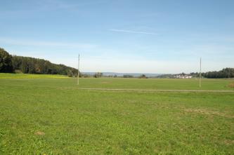 Unter einem weiten blauen Himmel dehnt sich eine ebenso weite Grünfläche aus. Sie wird links und rechts von Waldzungen eingefasst.