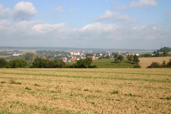 Blick über hellbraune Äcker auf eine tiefer liegende Hügellandschaft mit Wiesen, Feldern, Siedlungen und Wäldern. In der Ferne sind flache bewaldete Höhen erkennbar.