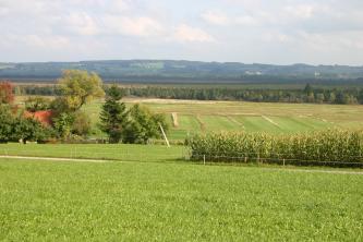 Weiter Blick über grüne Wiesen auf einen breiten Gürtel von Wald- und Moorflächen. Im Hintergrund erheben sich bewaldete Hügel und Berge.