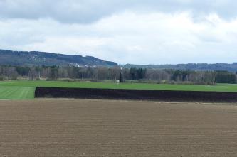 Blick auf eine ebene Landschaft mit Äckern, Wiesen und schwarzen Moorböden. Im Hintergrund Waldstreifen sowie bewaldete Hügel und Berge.