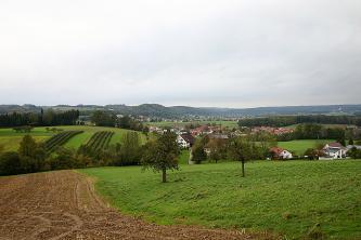 Blick über eine wellenartig geformte Acker- und Wiesenlandschaft mit Waldstreifen, einer Siedlung in der Mitte und bewaldeten Höhen im Hintergrund.
