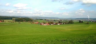 Blick über eine flachwellige Wiesenlandschaft mit Siedlungen und bewaldeten Höhenrücken im Hintergrund.