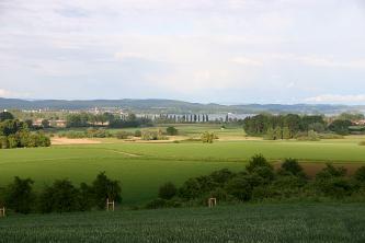 Blick von einem leicht erhöhten Standort auf eine flache Landschaft mit Wiesen, Bäumen und einer moorigen Senke. Im Hintergrund ein großer See, eine Stadt und bewaldete Höhen.
