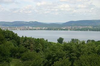 Blick über einen Wald auf einen See. Im Hintergrund sind Siedlungen sowie bewaldete Höhenzüge erkennbar.