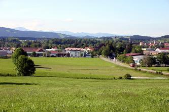Blick von einer Anhöhe auf flache grüne Wiesen, Siedlungen, Bäume und bewaldete Hügel. Im Hintergrund verläuft eine Gebirgskette.