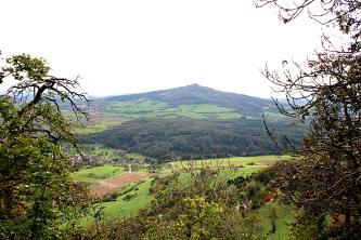 Blick durch Bäume hindurch über eine Landschaft mit Feldern, Wiesen, Siedlungen und Waldstücken auf einen bewaldeten Vulkankegel.