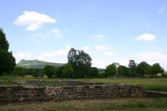 Im Vordergrund befindet sich vor ein paar Bäumen ein altes Mauerwerk. Im Hintergrund ist ein Hügel zu sehen.