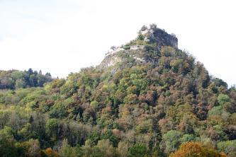 Vor hellem Himmel befindet sich ein bewaldeter Vulkankegel. Auf der Kuppe sind die Reste einer Burg verstreut.