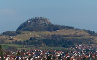 Im Hintergrund liegt eine Felskuppe, auf der eine Ruine steht. Vorne befindet sich eine Ortschaft.