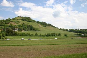 Blick über Ackerflächen, Reben und eine Straße auf einen vereinzelt bewaldeten, von einer Burg gekrönten Hügel.