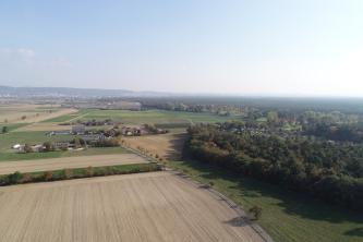 Unter einem wolkenlosen Himmel breiten sich links ausgedehnte Äcker und Wiesen, rechts Wälder und Schrebergärten aus. Im Hintergrund links bewaldete Berge, davor eine größere Siedlung.