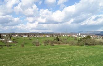 Unter einem wolkigen Himmel breitet sich eine wellige Hochfläche mit Wiesen, Feldern, Bäumen und Siedlungen aus. Im Hintergrund teils bewaldete Berge.