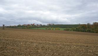 Das Bild zeigt abgeerntete, nach rechts abfallende braune Äcker. Im Hintergrund ein Gegenhang mit Grünkulturen. Dazwischen stehen rechts ein paar Obstbäume.
