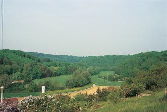 Über hochgelegene Wiesen und Streuobstbäume geht der Blick auf ein Flusstal mit Wiesen, Feldern und Bäumen. Rechts und links sowie zum Hintergrund hin steigen bewaldete Hänge empor.
