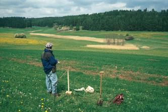 Das Foto zeigt ein wannenförmiges Tal mit Grünland und Löwenzahn. Von der Bildmitte bis zum Hintergrund zieht sich ein schmaler Streifen Schilf. Der Hintergrund ist bewaldet. Vorne steht ein Bodenkundler mit Bohrstock, Hammer und Spaten.