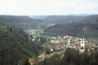 Von erhöhtem Standpunkt aus blickt man über die Dächer einer Stadt auf eine sich windende Flussaue. I)m Vordergrund links sowie im Hintergrund erheben sich bewaldete Anhöhen.