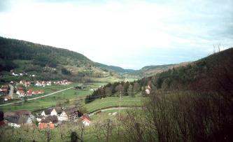 Von erhöhtem Standpunkt aus blickt man über kahle Obstbäume auf eine in einem Tal liegende Siedlung. Nach rechts hin erhebt sich ein terrassierter, bewaldeter Hang. Auch links und im Hintergrund sind Waldhänge erkennbar.