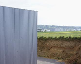 Das zweigeteilte Bild zeigt rechts einen angeschnittenen, hohen braunen Ackerboden und links die Fassade einer modernen Fabrikhalle. Im Hintergrund rechts sind weitere Industriebauten erkennbar.