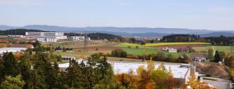 Blick über Industriebauten einer größeren Stadt mit angrenzenden Acker- und Waldflächen. Im Hintergrund sind mehrere bewaldete Höhenzüge erkennbar.